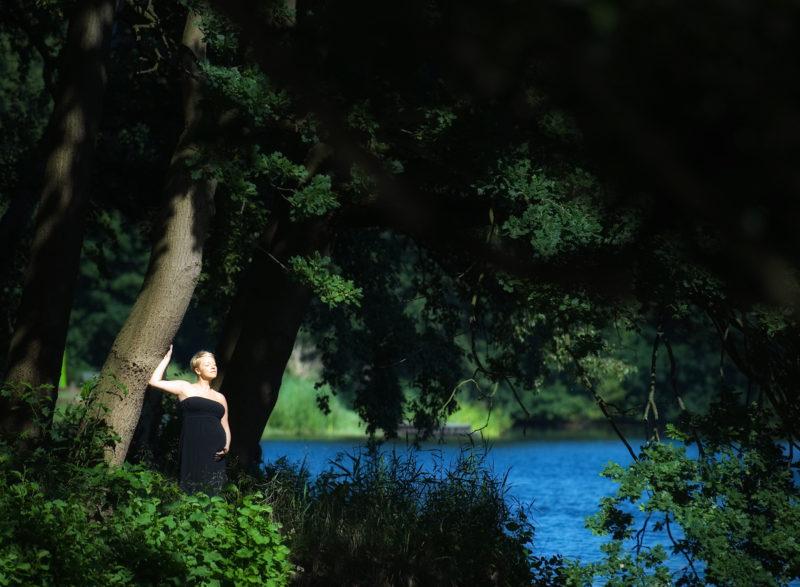 Schwangere unter Baum am See